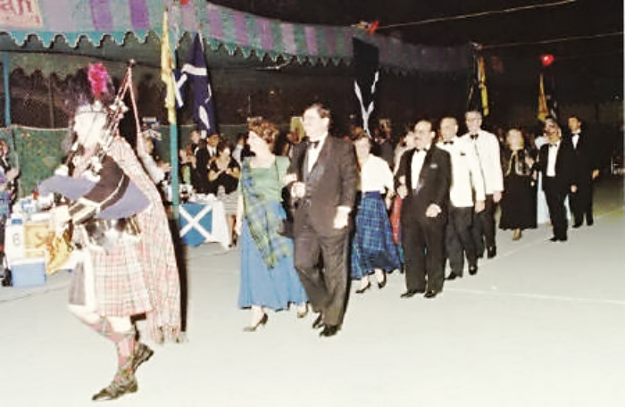 A photograph of Mushtaq Talpur in a Grand March prior to Scottish country dancing at St. Andrews Ball, organized by the Caledonian Society, Karachi.